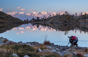 A panoramic view of the Alpine range overlooking the Mont Avic Natural Parc reflecting in a small laの写真素材 [FYI03773086]