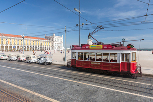 A typical red tram stops at the historical Praca Do Comercio square near the Tagus river, Lisbon, Esの写真素材 [FYI03773094]