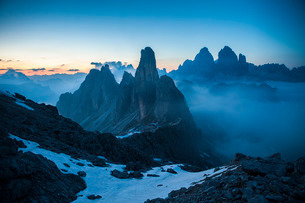 The Cadini di Misurina emerging from the fog after sunset, in a typical Dolomitic landscape, Dolomitの写真素材 [FYI03773108]