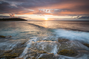 Waves crash on cliffs under a colorful Caribbean sunset, Galley Bay, St. John's, Antigua, Antigua anの写真素材 [FYI03773110]