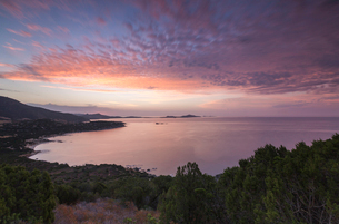 The colors of sunrise are reflected on the sea around the beach of Solanas, Villasimius, Cagliari, Sの写真素材 [FYI03773142]