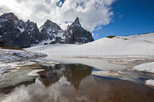 Snow is thawing leaving some puddles at the foot of the Pale di San Martino by San Martino di Castroの写真素材 [FYI03773160]