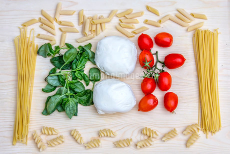 Composition with the bright colours of Italian food: pasta, spaghetti, tomatoes from Sicily, mozzareの写真素材 [FYI03773174]