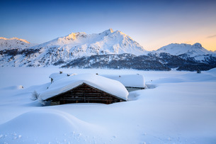 Some scattered huts in a snowy landscape at Spluga by the Maloja Pass with the magical colors of theの写真素材 [FYI03773206]