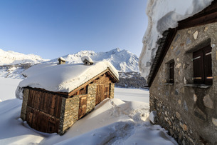 The sun, covered with thin clouds, illuminating a typical hut covered with snow at the Maloja Pass,の写真素材 [FYI03773216]