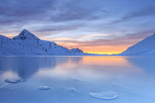 The colors of dawn invading the smooth surface of Lago Bianco exceptionally icy, Bernina Pass, Graubの写真素材 [FYI03773217]