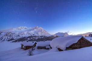 A starry night covering the Spluga huts submerged in snow near the Maloja Pass, Graubunden, Swiss Alの写真素材 [FYI03773218]
