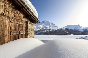 The sun, covered by thin clouds, illuminating a typical hut covered with snow at the Maloja Pass, Grの写真素材 [FYI03773220]