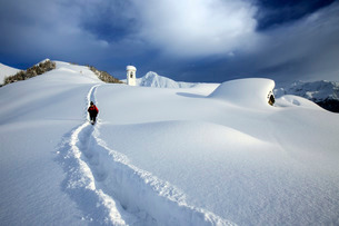 A solitary hiker leaving the little village at the Scima Alp covered in snow, Valchiavenna, Lombardyの写真素材 [FYI03773236]