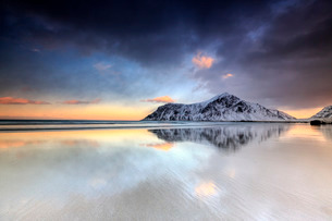 Sunset on Skagsanden beach surrounded by snow covered mountains reflected in the cold sea, Flakstad,の写真素材 [FYI03773326]
