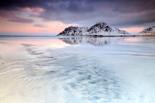 Sunset on Skagsanden beach surrounded by snow covered mountains reflected in the cold sea, Flakstad,の写真素材 [FYI03773334]