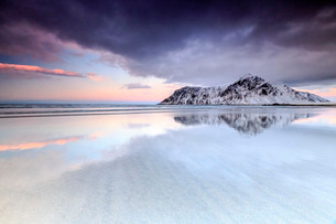 Sunset on Skagsanden beach surrounded by snow covered mountains reflected in the cold sea, Flakstad,の写真素材 [FYI03773337]