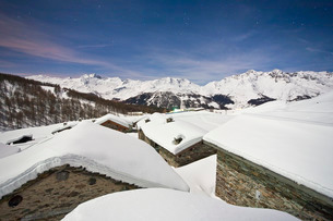 Group of mountain huts covered in snow under a starry night in Valle Spluga, Vachiavenna, Lombardyの写真素材 [FYI03777107]