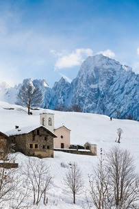 The tiny village of Daloo in Valchiavenna, with its bell tower and church, after a heavy snowfall, Lの写真素材 [FYI03777110]