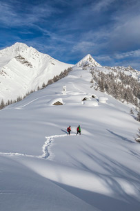 Hikers trying to approach the little village at the Scima Alp covered in snow, Valchiavenna, Lombardの写真素材 [FYI03777137]