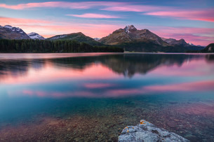 Pink sky at dawn illuminates the peaks reflected in Lake Sils, Engadine, Canton of Graubundenの写真素材 [FYI03777198]