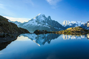 The snowy peaks of Mont Blanc are reflected in the blue water of Lac Blanc at dawn, Chamonix, Hauteの写真素材 [FYI03777242]
