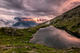 Clouds are tinged with purple at sunset at Lac de Cheserys, Chamonix, Haute Savoie, French Alpsの写真素材 [FYI03777244]