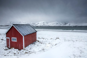 A typical house of the fishermen called rorbu on the snowy beach frames the icy sea at Ramberg, Lofoの写真素材 [FYI03777268]
