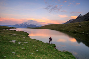 Hiker on the shore admires the pink colors of dawn reflected in Lake Campagneda, Malenco Valley, Valの写真素材 [FYI03777310]