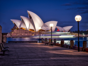 A boat passes by the Sydney Opera House, during blue hour, Sydney, New South Walesの写真素材 [FYI03777701]