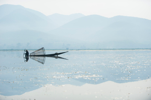 A basket fisherman on Inle Lake scans the still and shallow water for signs of life, Shan Stateの写真素材 [FYI03777863]