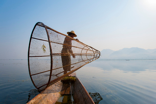 A basket fisherman on Inle Lake prepares to plunge his cone shaped net, Shan Stateの写真素材 [FYI03777866]