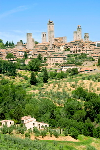 View to town across agricultural landscape, San Gimignano, Tuscanyの写真素材 [FYI03778022]