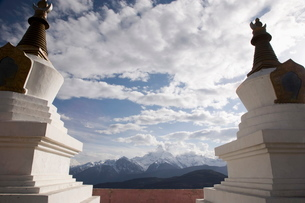 Buddhist stupas on way to Deqin, on the Tibetan Border, with the Meili Snow Mountain peak in the bacの写真素材 [FYI03778307]