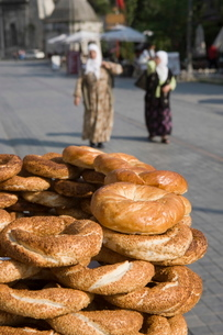 Traditional Turkish bagels with sesame seeds for sale, ladies in traditional costume in distance, Isの写真素材 [FYI03778925]