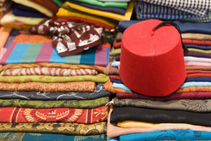Colourful cotton fabric and a traditional fez for sale in a shop in Luxorの写真素材 [FYI03779205]