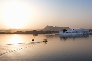 Boat going out to Lake Palace Hotel at dusk, the hotel is situated in the middle of Lake Pichola, inの写真素材 [FYI03779270]