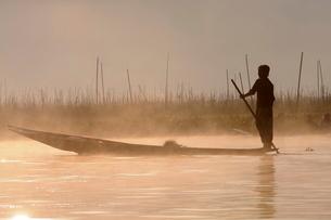 Man rowing his little rowing boat at sunrise on Inle Lake, Shan States, Myanmarの写真素材 [FYI03780595]