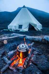 Boiling water pot over an open fire on a campsite and tipi on Tolbachik volcano, Kamchatka, Russia,の写真素材 [FYI03780862]