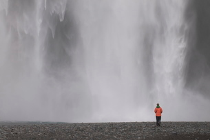 Young woman admiring the big waterfall of Skogarfoss, Icelandの写真素材 [FYI03781074]