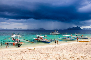 Outrigger boats before a strom anchoring on a sandy beach  in  the Bacuit archipelago, Palawan, Philの写真素材 [FYI03781238]
