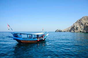 Tourist boat in form of a dhow sailing in the Khor ash-sham fjord, Musandam, Oman, Middle Eastの写真素材 [FYI03781290]