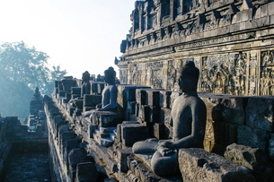 Early morning light shining on Buddhas sitting in the temple complex of Borobodur, Java, Indonesia,の写真素材 [FYI03781328]