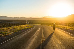 Woman walking down a long winding road at sunset in eastern Nevada'の写真素材 [FYI03781486]