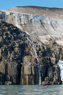 Tourist in a zodiac looking at Waterfall dropping in the ocean, Alkerfjellet, Svalbard, Arcticの写真素材 [FYI03781678]