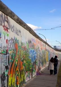 Couple walking along the East Side Gallery Berlin Wall mural, Berlinの写真素材 [FYI03783057]