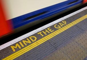 MIND THE GAP sign on platform edge Undergroundの写真素材 [FYI03783082]