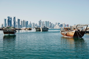 Downtown Doha with its impressive skyline of skyscrapers and authentic dhows in the bay, Doha, Qatarの写真素材 [FYI03783127]