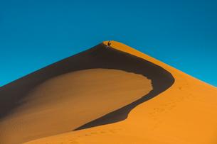 Woman hiking up the giant Sand Dune 45, Sossusvlei, Namib-Naukluft National Park, Namibia, Africaの写真素材 [FYI03783245]