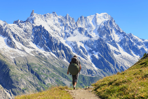 Hiker runs along trail with views on Grandes Jorasses and the Giant Tooth, Veny Valley, Courmayeur,の写真素材 [FYI03783995]