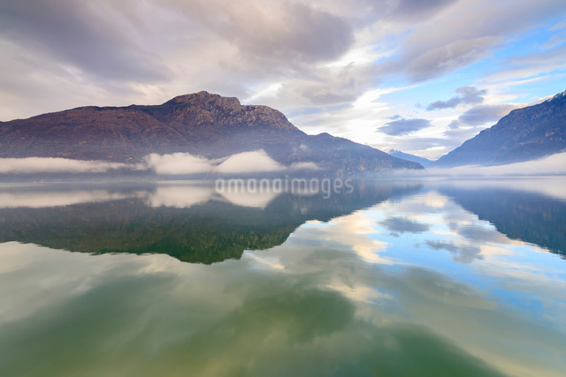 Mountains reflected in Lake Mezzola at dawn shrouded by mist, Verceia, Chiavenna Valley, Lombardy, Iの写真素材 [FYI03784089]