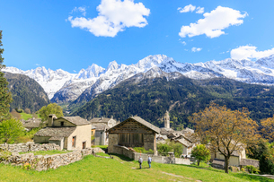 View of Soglio between meadows and snowy peaks in spring, Maloja, Bregaglia Valley, Engadine, cantonの写真素材 [FYI03784300]