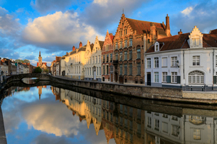Pink clouds at dawn on the Belfry and historic buildings reflected in the typical canal, Bruges, Wesの写真素材 [FYI03784475]