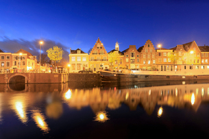 Dusk lights on typical houses and bridge reflected in a canal of the River Spaarne, Haarlem, North Hの写真素材 [FYI03784477]