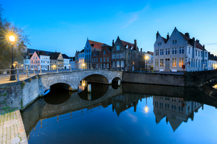 Dusk lights on the historic buildings of the city centre reflected in the typical canals, Bruges, Weの写真素材 [FYI03784480]